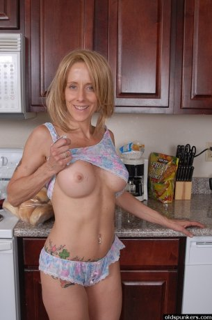 Mature lady in tattoo and piercing masturbates in the kitchen